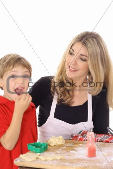 little boy eating cookie batter isolated on white