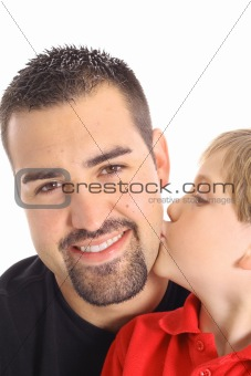shot of a little boy kissing father