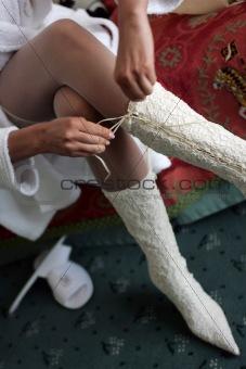 Bride tying wedding boots