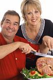 shot of a beautiful couple slicing ham
