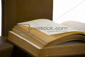Old book with yellowing pages open and laying flat with words out of focus. This book is laying on a stack of books with one sitting upright in the background. All Osilated on white with clipping path.