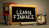 Handwritten Learn Finance on a Chalkboard.