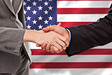 Composite image of close up of two businesspeople shaking their hands
