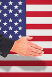 Composite image of businessman holding his hand out