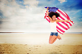 Composite image of pretty girl wrapped in american flag jumping and smiling at camera