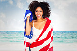 Composite image of pretty girl wrapped in american flag smiling at camera