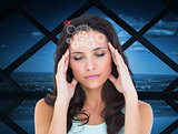Composite image of pretty brunette with a headache