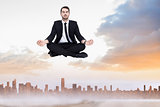 Composite image of peaceful businessman sitting in lotus pose relaxing