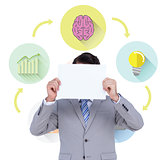 Composite image of businessman holding blank sign in front of his head