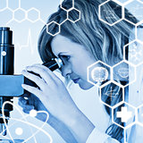 Composite image of attractive blonde scientist looking through a microscope