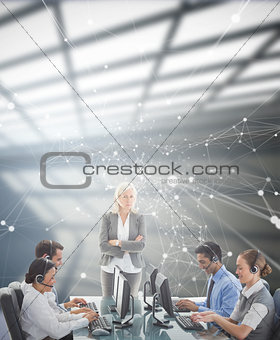 Composite image of unhappy businesswoman monitoring her colleagues