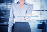 Composite image of businesswoman holding digital tablet