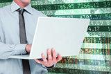 Composite image of businessman using a laptop