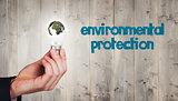 Composite image of hand holding environmental light bulb