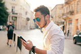 Outdoor portrait of modern young man with mobile phone in the street.