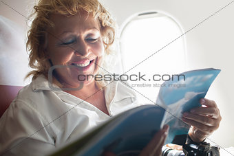 Mature Woman Reading Magazine on a Plane
