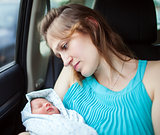 Woman holding newborn baby sitting in the car