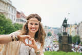 Bohemian woman tourist in Prague showing heart shaped hands