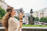 Joyful trendy hippie woman tourist with retro camera in Prague