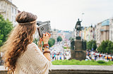 Trendy hippie woman tourist with vintage retro camera  in Prague
