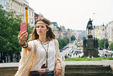 Trendy hippie woman making selfie on Wenceslas Square, Prague