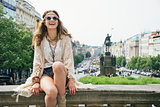 Laughing trendy hippie woman relaxing on stone parapet in Prague