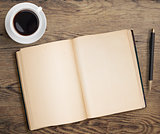 Open book with pen and coffee cup on old wooden table