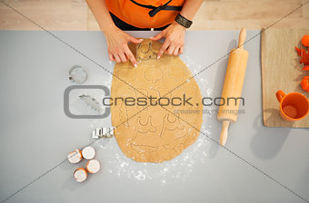 Housewife cutting out biscuits for Halloween party. Closeup
