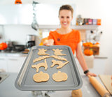Closeup on woman holding tray of uncooked Halloween biscuits
