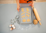 Closeup on housewife with tray of uncooked Halloween biscuits