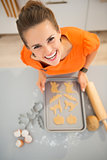 Smiling housewife holding tray of uncooked Halloween biscuits