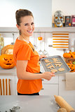 Cheerful woman holding tray of uncooked Halloween biscuits