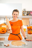 Smiling halloween dressed woman with rolling pin in kitchen