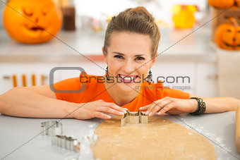 Housewife cutting out Halloween cookies in kitchen
