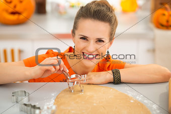 Housewife holding pastry cutter for Halloween biscuits