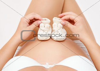 Pregnant woman holding a pair of tiny shoes