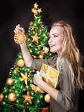 Happy girl decorating Christmas tree