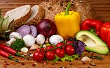 Fresh vegetables and spices: tomatoes, peppers, mushrooms, herbs, bread, avocado on wooden background
