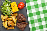 Steak with grilled potato, corn, salad and tomato