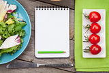 Fresh healthy salad, tomatoes and notepad for copy space