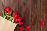 Red tulips bouquet in bag over wood