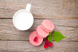 Colorful raspberry macaron cookies and cup of milk