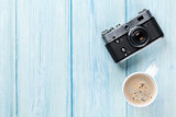 Travel camera and coffee cup on wooden table