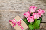 Pink roses and valentines day gift box over wooden table