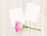 Two blank photo frames and pink rose