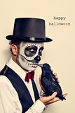 man with calaveras makeup and crow, and text happy halloween