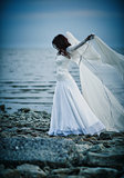 Beautiful sad girl in white dress standing on sea shore