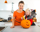 Halloween dressed girl with mother preparing Jack-O-Lantern