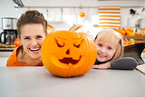 Funny mother with daughter in Halloween decorated kitchen