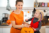 Girl in bat costume with mother preparing Jack-O-Lantern